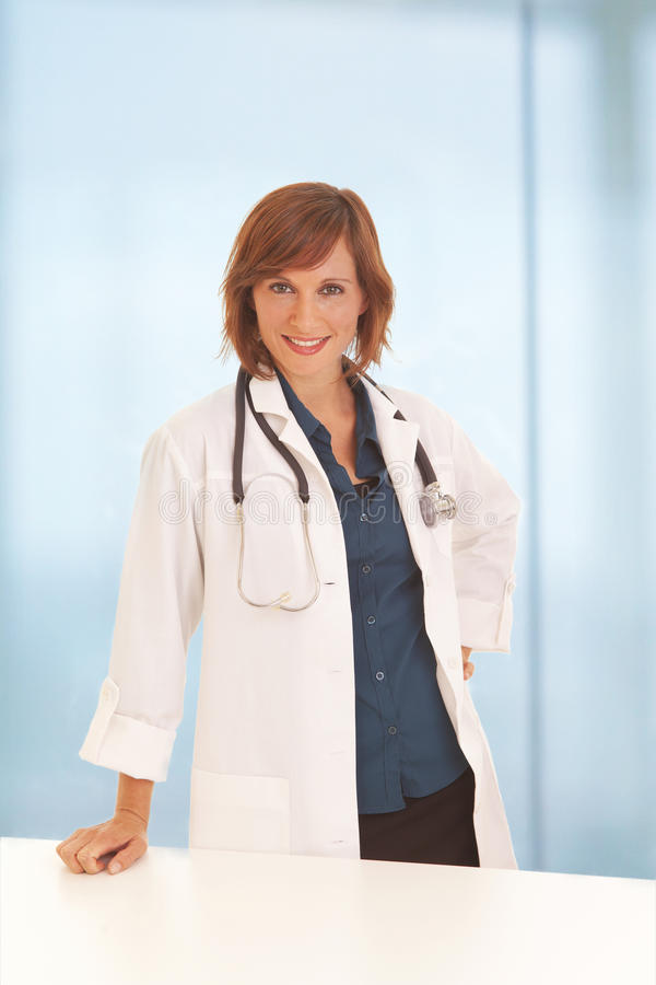 Woman doctor leaning on desk stock photo