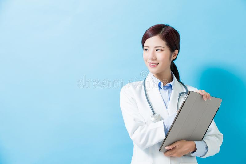 Woman doctor look somewhere. And take tablet pc on the blue background stock images