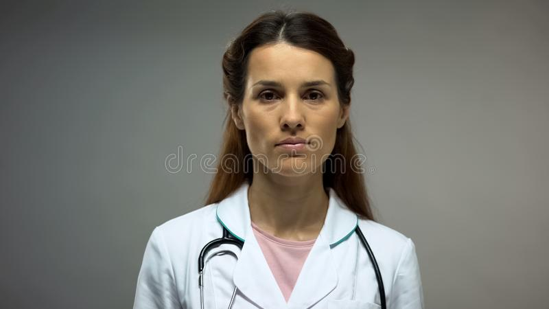 Woman doctor looking into camera, HIV AIDS prevention campaign, information stock images
