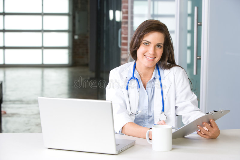 Woman doctor in a modern office. Woman doctor holding a chart in a modern office stock photo