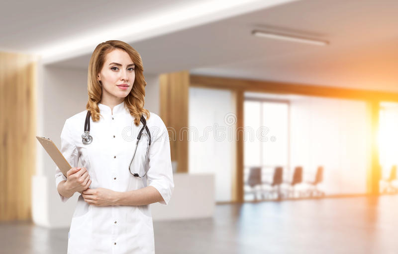 Woman doctor in an office lobby. Portrait of a woman doctor standing with her clipboard in an office lobby. Toned image royalty free stock photo