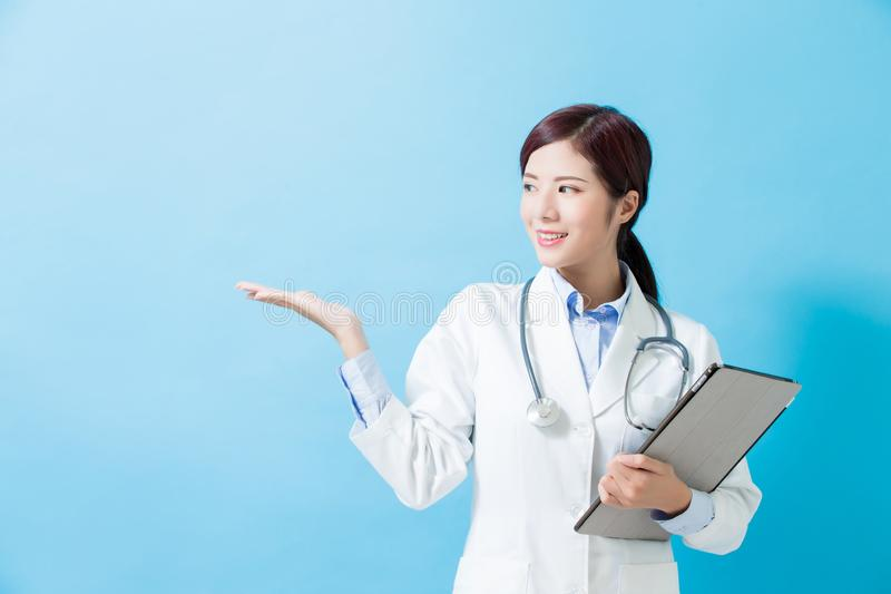Woman doctor show something. And take tablet pc on the blue background stock images