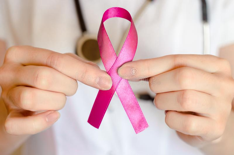 Woman doctor keeps a pink ribbon close up. Breast cancer examination concept royalty free stock photos