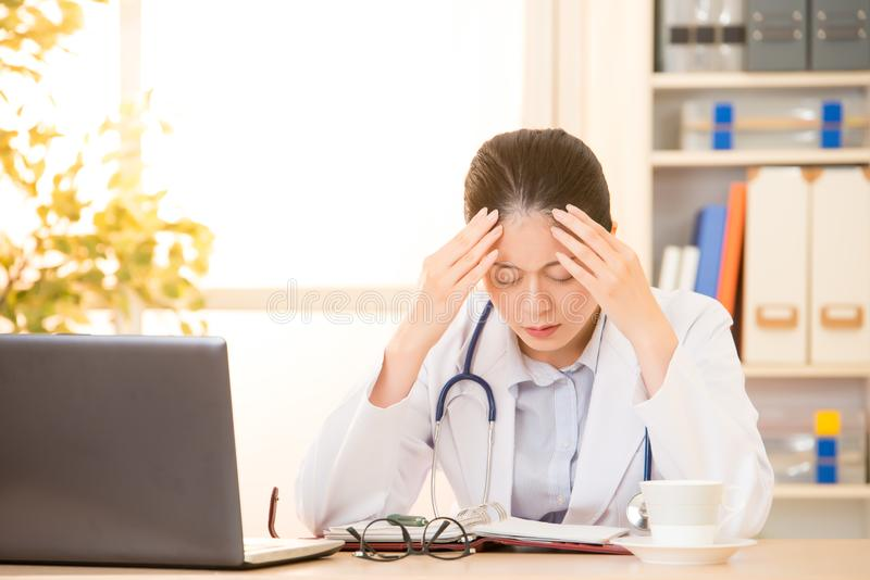 Woman doctor stressed with headache. Woman doctor stressed with migraine headache overworked. Health care professional in lab coat wearing stethoscope at stock images