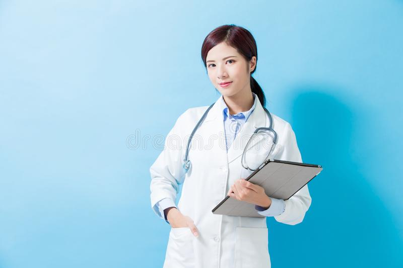 Woman doctor take tablet pc. Woman doctor smile to you and take tablet pc on the blue background stock photography