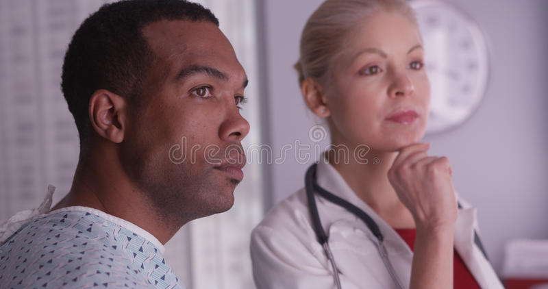 Woman doctor talking about xrays to black patient.  stock photography