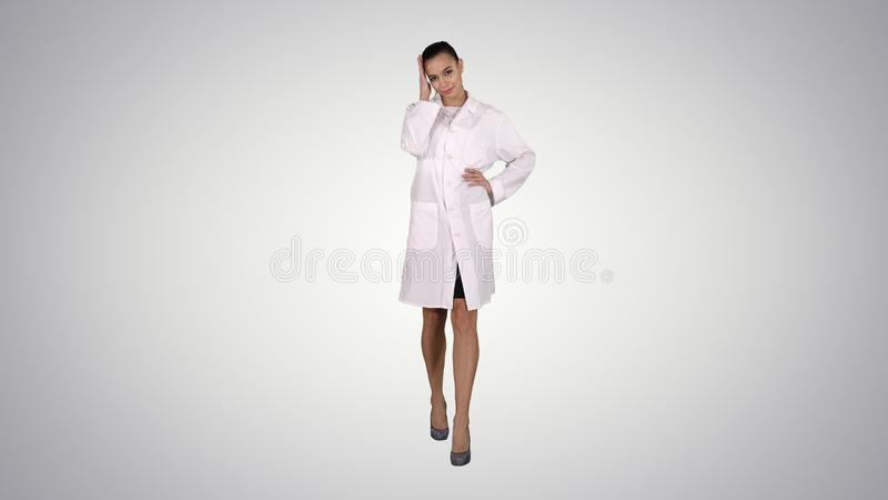 Woman doctor walking like fashion model on gradient background. royalty free stock images