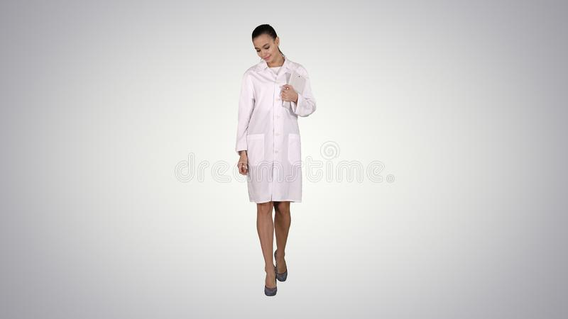 Woman doctor walking with tablet in hands on gradient background. royalty free stock photography
