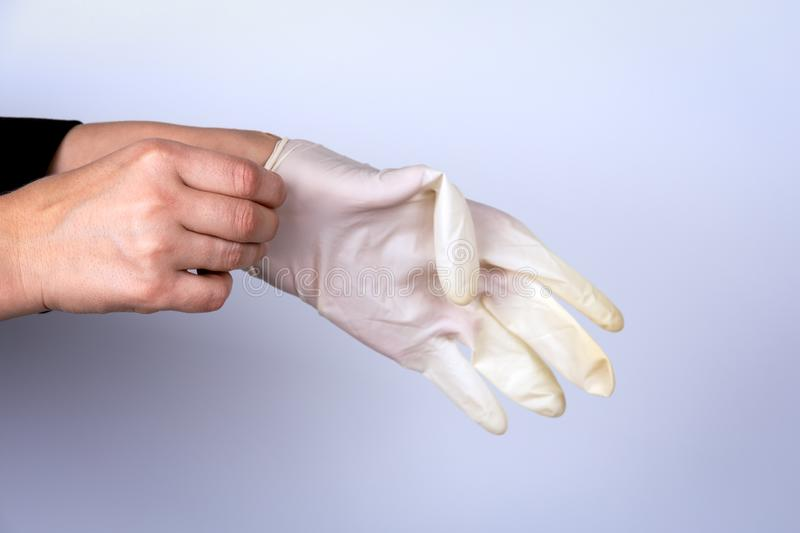 Woman doctor wears medical gloves stock image