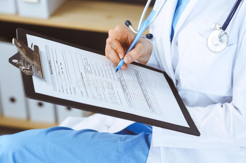 Woman doctor at work at hospital. Young female physician write prescription or filling up medical form while sitting in royalty free stock images