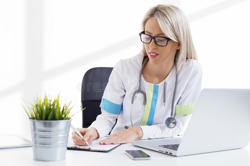 Woman doctor working in the office in clinic stock photography