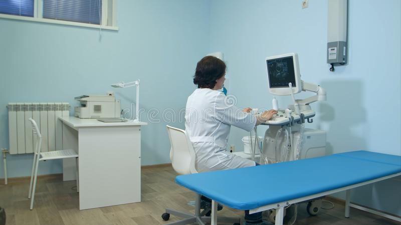 Woman doctor working at ultrasound diagnostic machine. Professional shot in 4K resolution. 096. You can use it e.g. in your commercial video, business stock photography