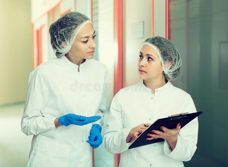 Woman doctors talking about beauty procedures royalty free stock images