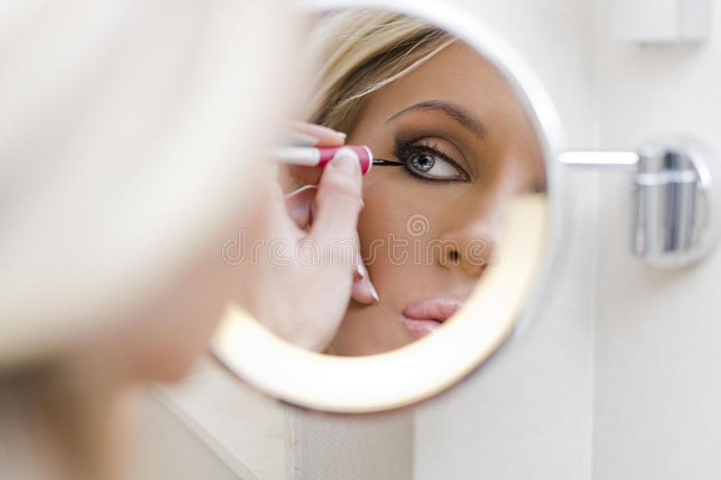 The woman does a make-up. Before a mirror royalty free stock images