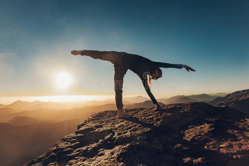 Woman does yoga exercises on cliff on Mount Sinai against background of sunrise. Woman does yoga exercises on edge of cliff on Mount Sinai against background of royalty free stock image