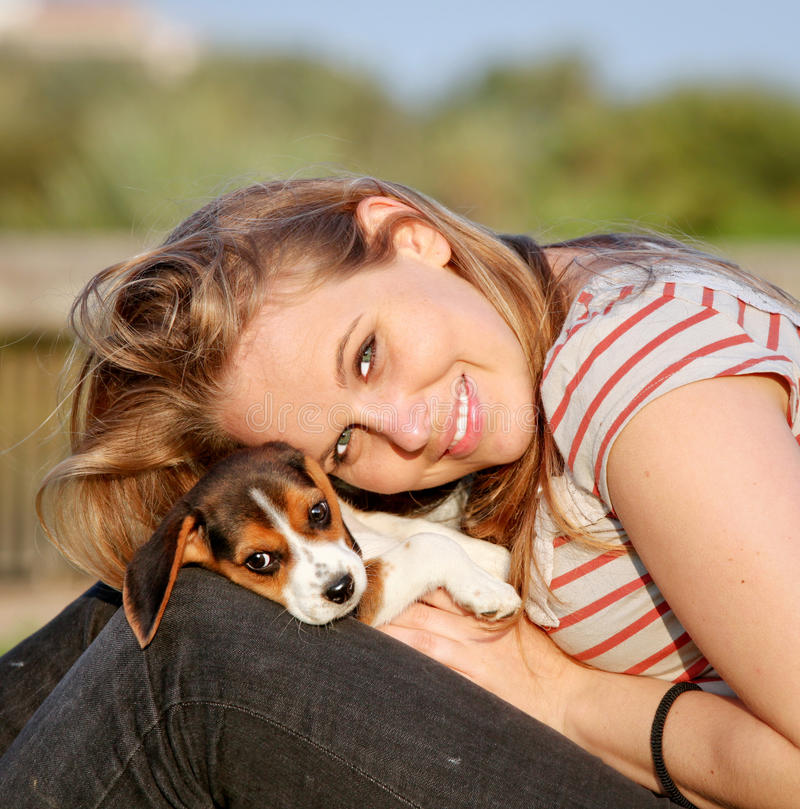 Woman and dog. Happy young woman with her pet beagle puppy dog outside