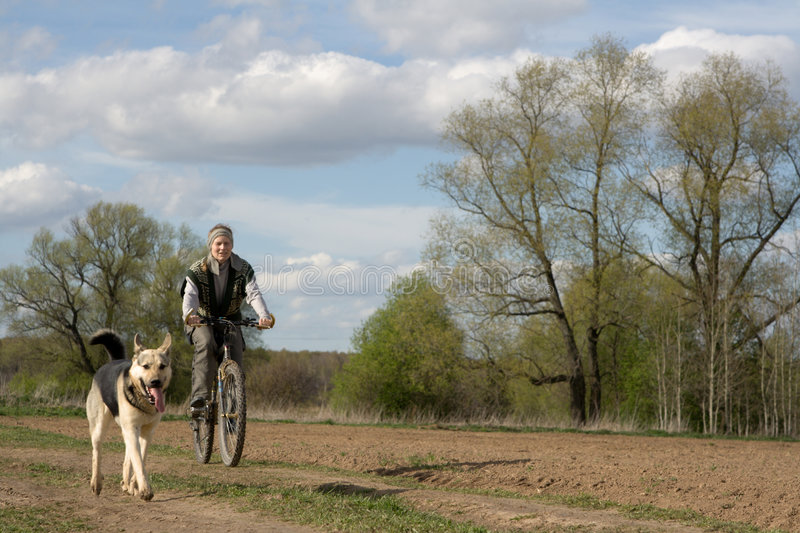 Woman with dog. Woman cycling with alsatian dog
