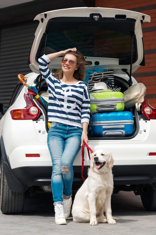 Woman with dog by car full of suitcases. royalty free stock photos