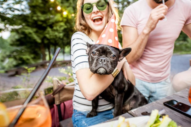 Woman with dog celebrating birthday. Happy women with french bulldog celebrating birthday with friends outdoors in the evening stock images