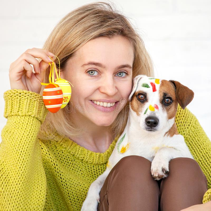 Woman and dog color Easter eggs. Female with pet royalty free stock image