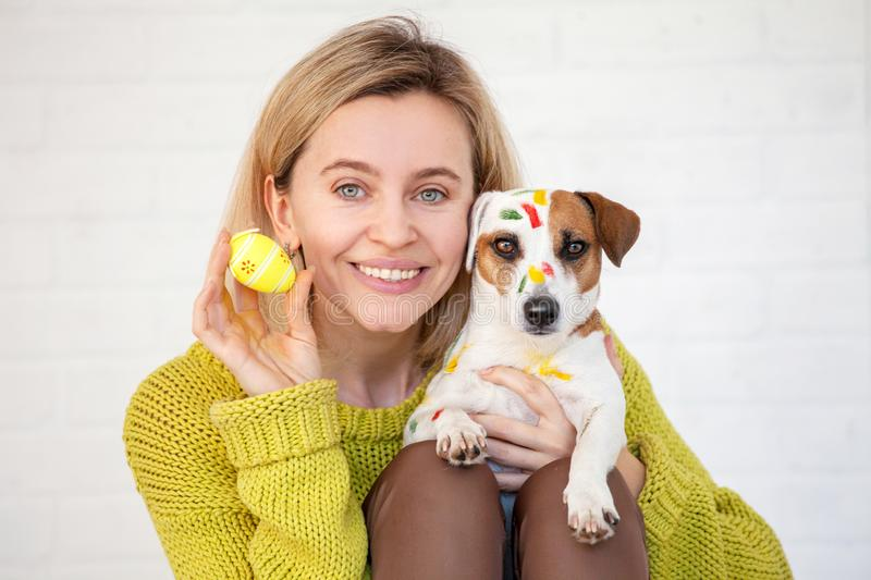 Woman and dog color Easter eggs. Female with pet royalty free stock photo
