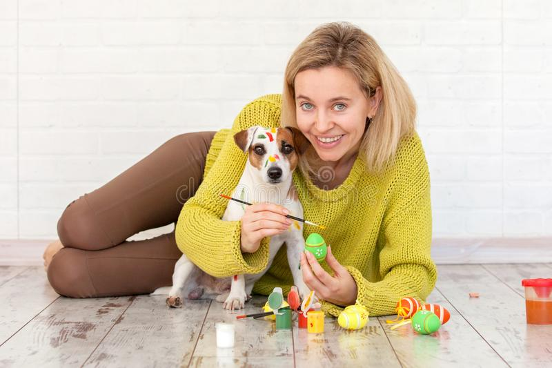 Woman and dog color Easter eggs. Female with pet painting royalty free stock image