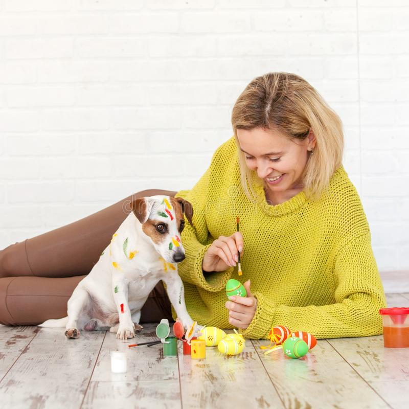 Woman and dog color Easter eggs. Female with pet painting stock photography