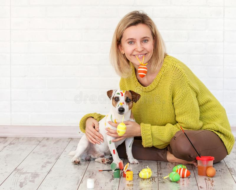 Woman and dog color Easter eggs. Female with pet painting royalty free stock photo