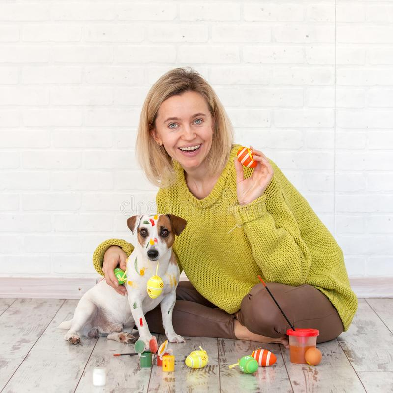 Woman and dog color Easter eggs. Female with pet painting stock images