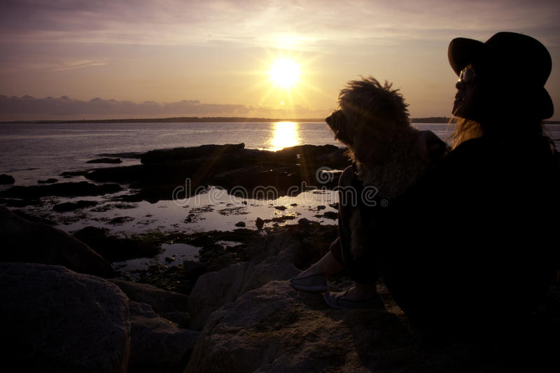 Woman and Dog Enjoy Beach Sunset royalty free stock photography