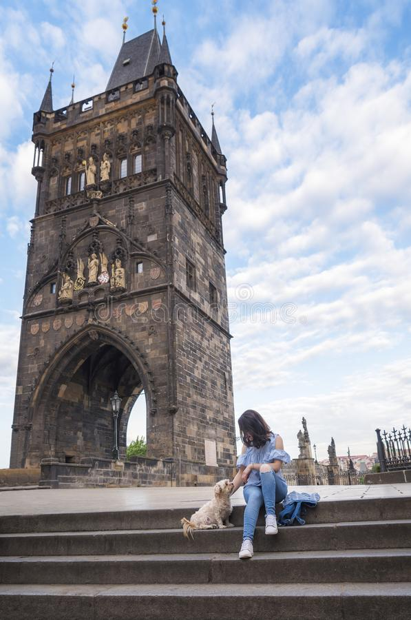 Woman with a dog in front of the tower of Charles Bridge royalty free stock images