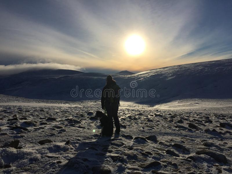 Woman and dog hiking in the mountains. A woman and her dog hiking in the snow in the mountains with sunset behind them royalty free stock image