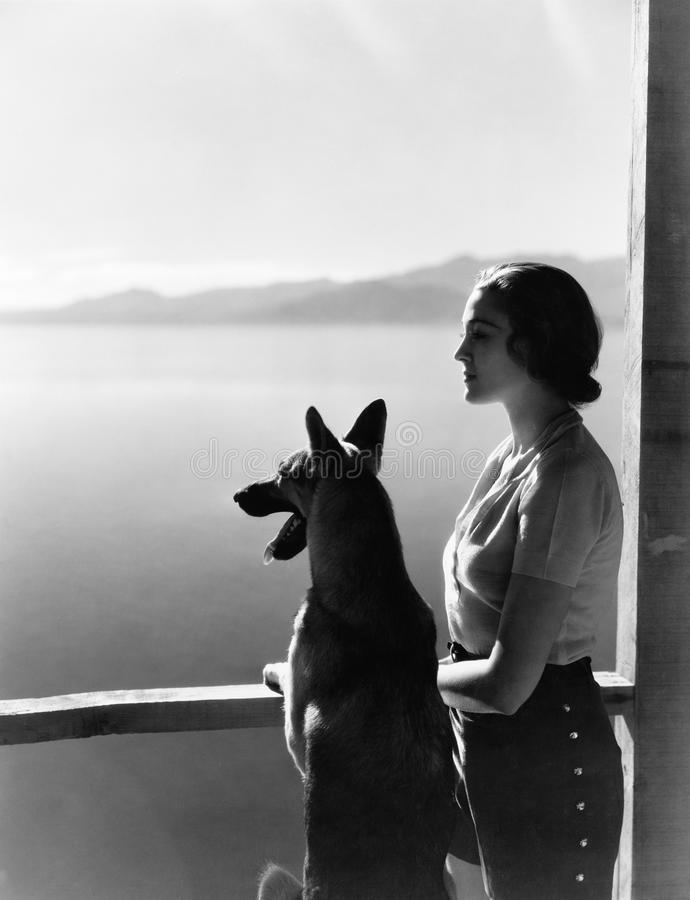 Woman and dog looking out over water royalty free stock images