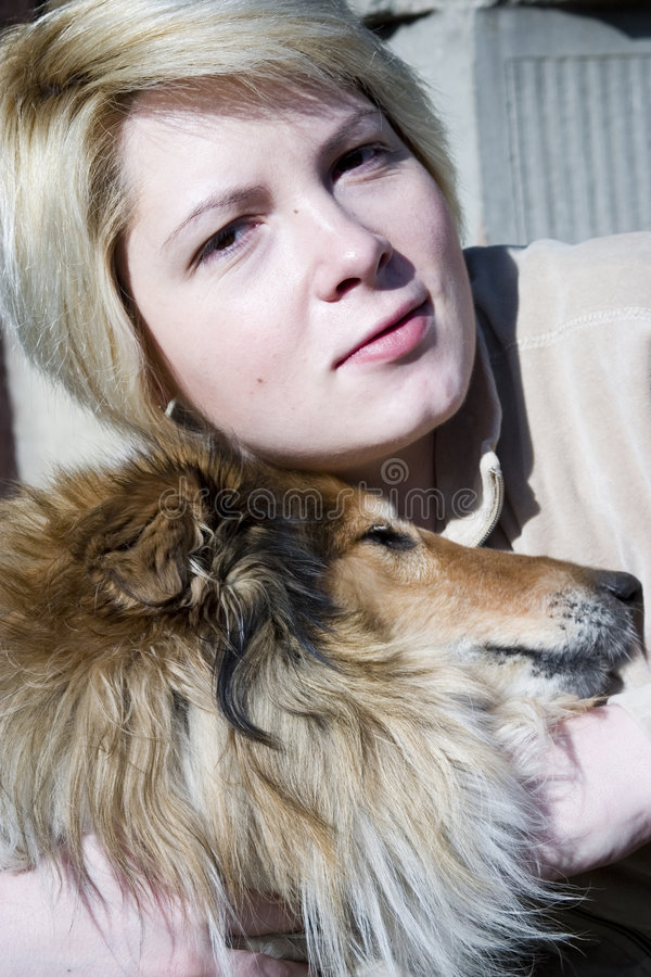 Woman and dog pet. A beautiful caucasian white woman head portrait with friendly facial expression hugging her beloved pet, a Collie dog royalty free stock photos