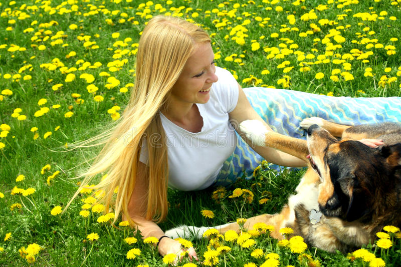 Woman and Dog Playing. A young woman and her German Shepherd dog laying in the grass playing stock photography