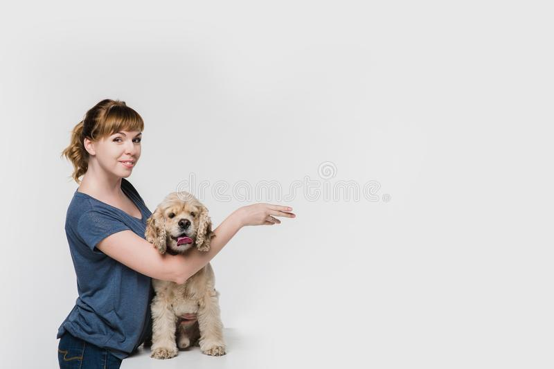 Woman with dog pointing to space at right stock photo