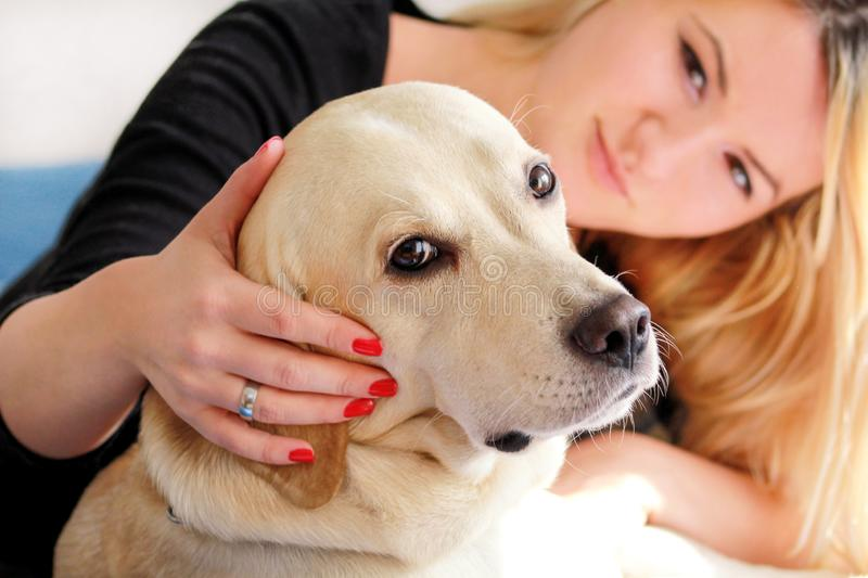 Woman with dog is resting in bed at home, relaxing in bedroom. Girl is petting with her dog. Portrait of cute yellow labrador. royalty free stock images