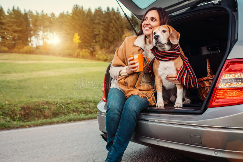 Woman and dog with shawls sits together in car trunk on autumn. Road stock photography