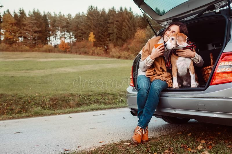 Woman with dog sit together in cat truck and warms цшер hot tea. Auto travel with pets concept image stock photography