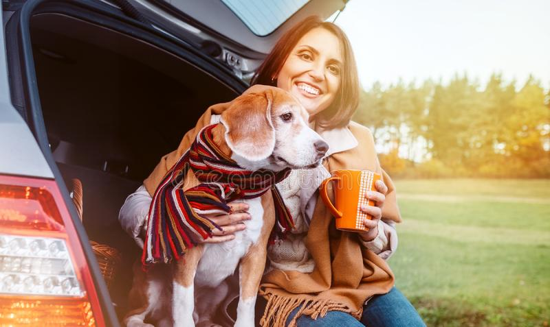 Woman with dog sit together in cat truck and warms цшер hot tea. Auto travel with pets concept image stock photos