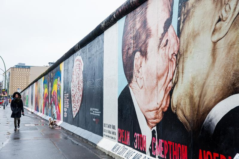 Woman and dog walking by the Wall Museum East Side Gallery on a cold end of winter day royalty free stock photography