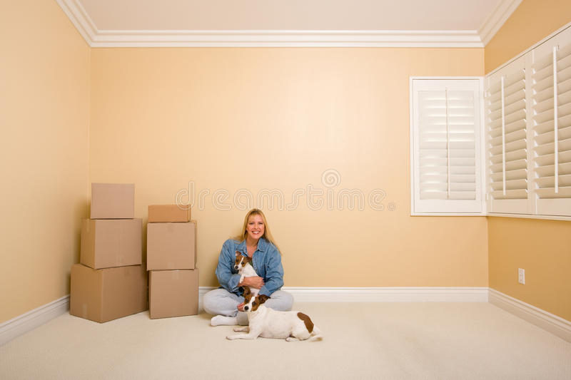 Woman and Dogs with Moving Boxes in Room on Floor. Pretty Woman and Dogs Sitting on the Floor with Moving Boxes in Empty Room stock photography