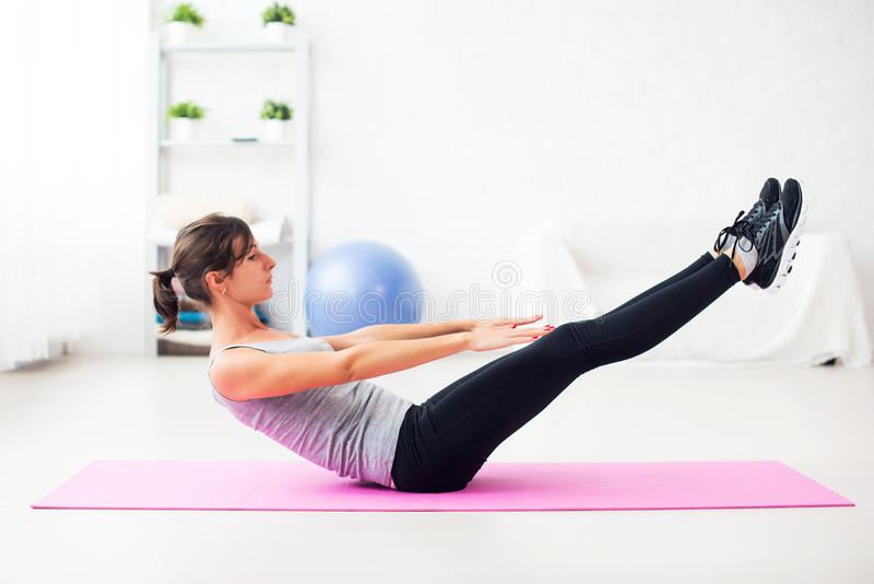 Woman doing abdominal exercise on mat at home royalty free stock photography