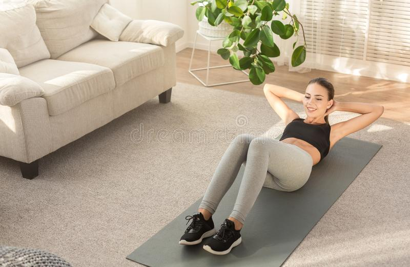Woman doing abs situps on floor at home. Home fitness concept. Woman doing abs crunches on floor at home, copy space stock images