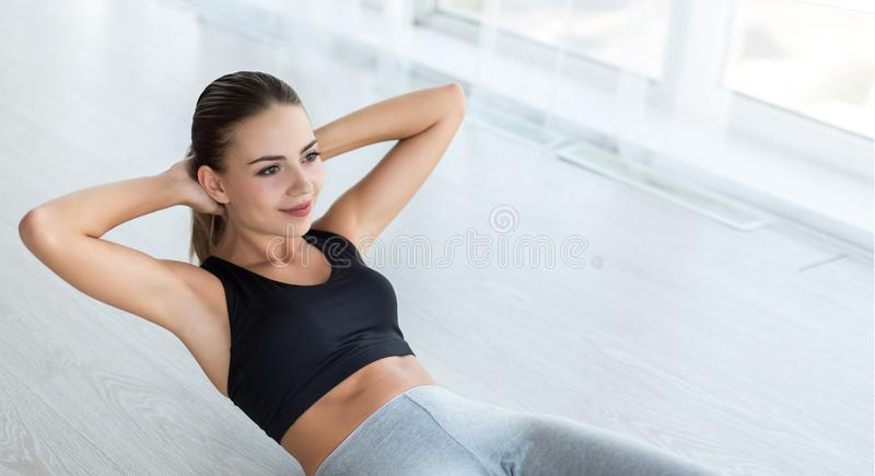 Woman doing abs situps on floor at home royalty free stock photography