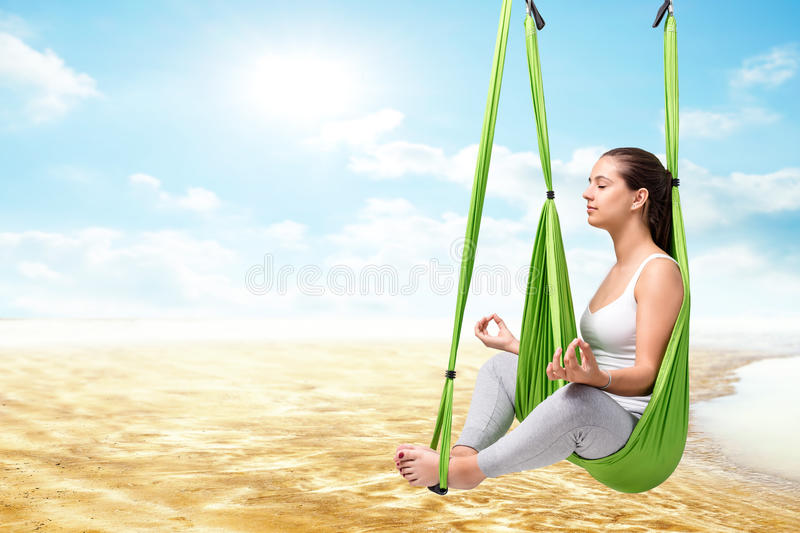 Woman doing aero yoga against seamless landscape. Conceptual portrait of young woman sitting in anti gravity yoga hammock with eyes closed.Girl doing spiritual royalty free stock images