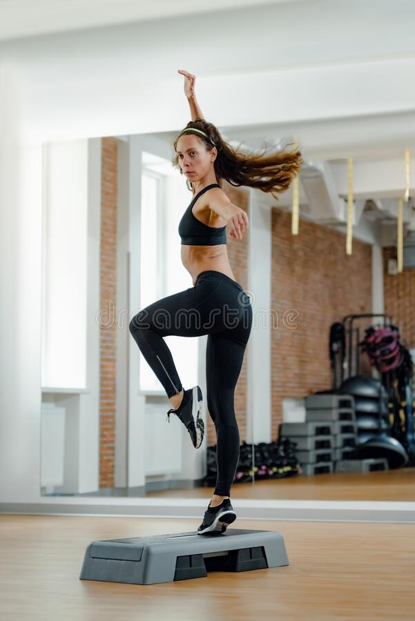 Woman doing aerobics. Attractive slim young woman doing aerobics with stepper royalty free stock image