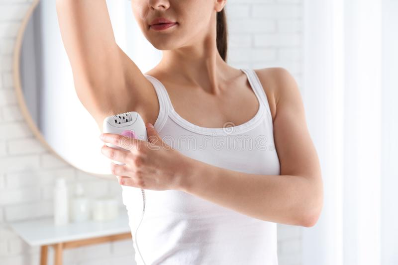 Woman doing armpit epilation procedure indoors, royalty free stock image