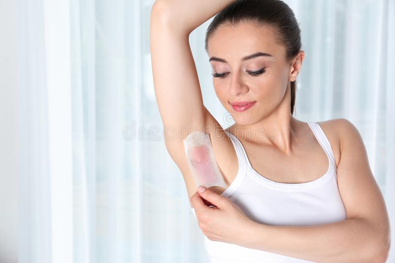 Woman doing armpit epilation procedure with wax strips indoors royalty free stock photography