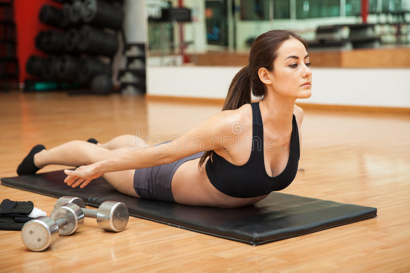 Woman doing a back curl at the gym royalty free stock photos